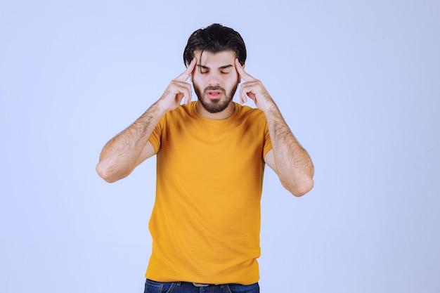 Mężczyzna w żółtej koszuli wygląda na wątpiącego i myślącego.