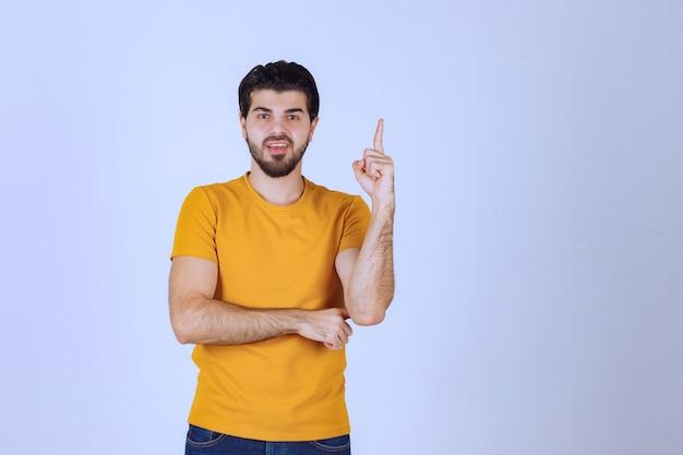Mężczyzna w żółtej koszuli wygląda na wątpliwego i myślącego.