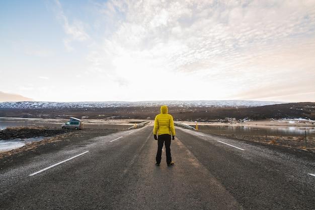 Mężczyzna w żółtej kurtce stojący na drodze otoczonej wzgórzami pokrytymi śniegiem na islandii