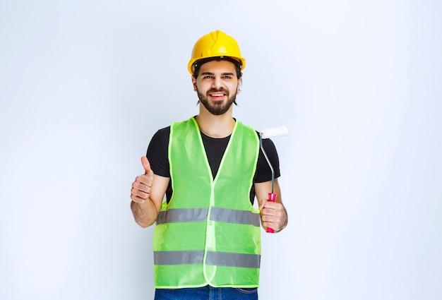 Mężczyzna w żółtym biegu trzyma wałek do malowania i czuje się usatysfakcjonowany.