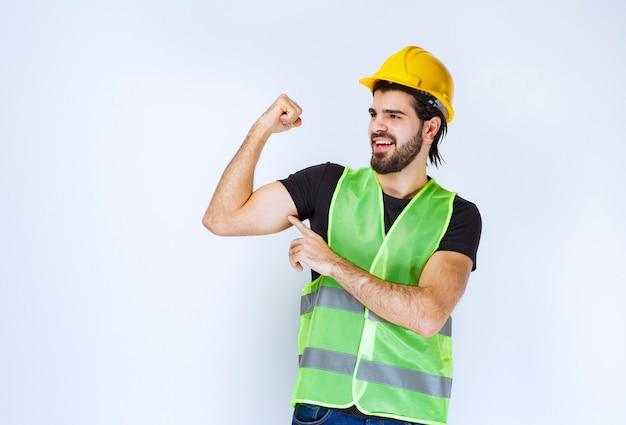 Mężczyzna w żółtym hełmie pokazujący jego mięśnie ramion.