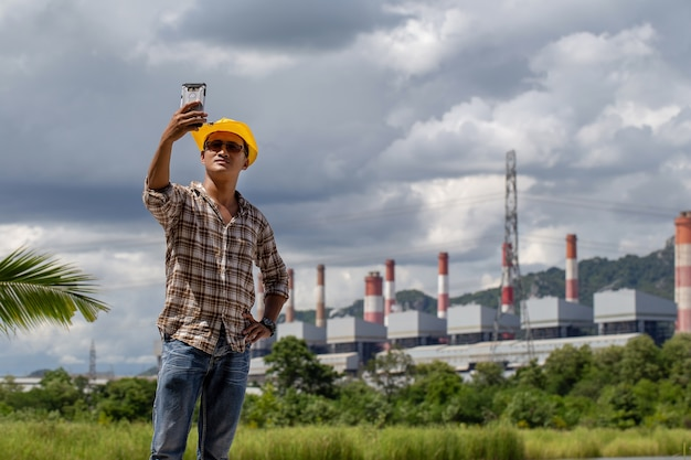 Mężczyzna w żółtym kapeluszu fotografował się z elektrownią w tle