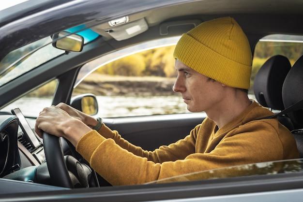 Mężczyzna w żółtym kapeluszu i swetrze jedzie samochodem wzdłuż rzeki i pięknego jesiennego lasu. pojęcie natury, podróży i jesiennego nastroju