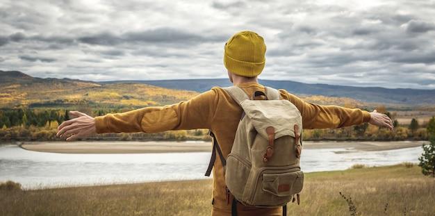 Mężczyzna w żółtym kapeluszu i swetrze z plecakiem stoi z wyciągniętymi na boki rękoma przed rzeką, jesiennym złotym lasem i wzgórzami. pojęcie wolności, podróży, wędrówek