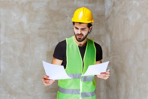 Mężczyzna w żółtym kasku i ekwipunku weryfikujący arkusze projektu