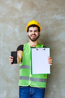 Mężczyzna w żółtym kasku i sprzęcie, trzymający plan projektu i pokazujący swój telefon