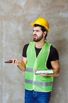 Mężczyzna w żółtym kasku i sprzęcie, trzymający plan projektu i rozmawiający z telefonem