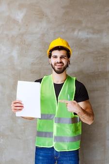 Mężczyzna w żółtym kasku i sprzęcie trzymający raporty z projektu
