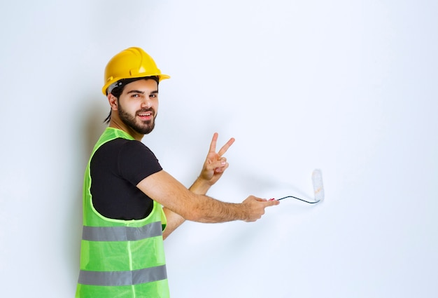 Mężczyzna w żółtym kasku maluje ścianę.