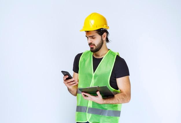 Mężczyzna w żółtym kasku sprawdza jego wiadomości.