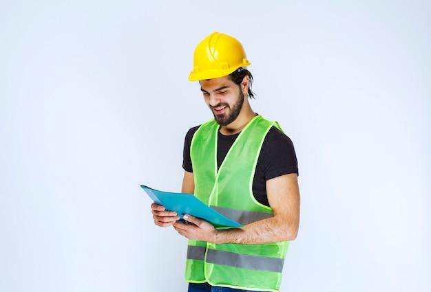 Mężczyzna w żółtym kasku trzyma i sprawdza niebieski folder projektu.