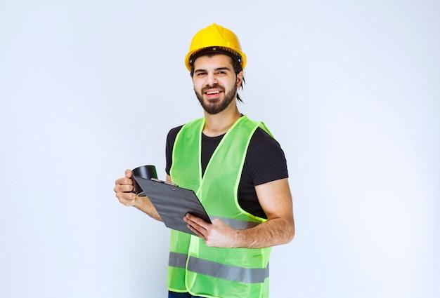 Mężczyzna w żółtym kasku trzymający folder projektu i filiżankę kawy.