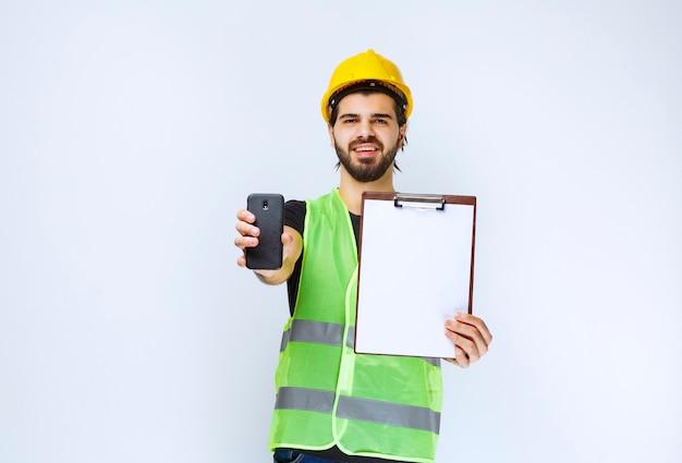 Mężczyzna w żółtym kasku trzymający folder projektu i smartfon.