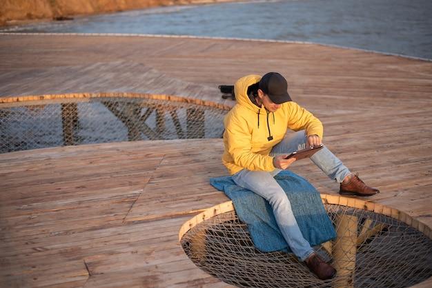 Mężczyzna w żółtym płaszczu przeciwdeszczowym i czarnej czapce siedzi na drewnianym molo, używa tabletu