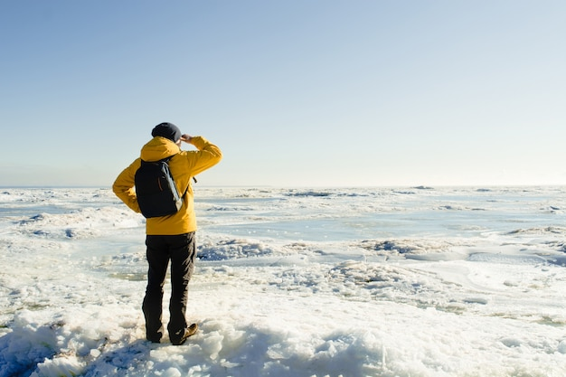 Mężczyzna w żółtym płaszczu przeciwdeszczowym z plecakiem stojący na zamarzniętym morzu i patrząc daleko