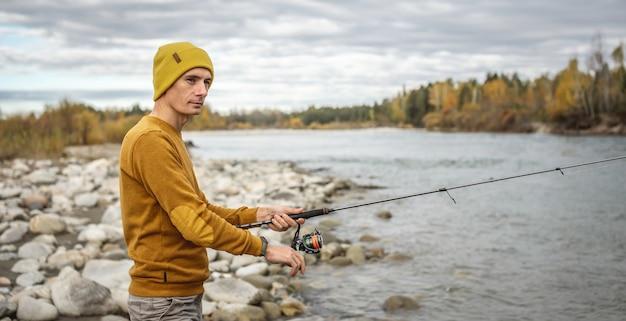 Mężczyzna w żółtym swetrze i czapce łowi wędkę na brzegu rzeki w jesiennym lesie z wędką spinningową w rękach