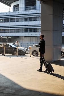 Mężczyzna w zwykłych ubraniach chodzący ze swoim bagażem