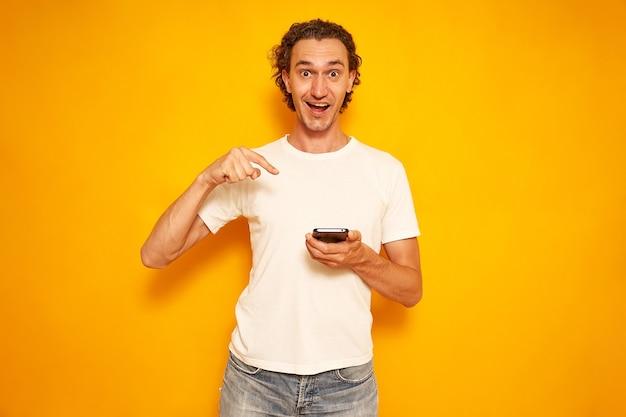 Mężczyzna w zwykłych ubraniach wskazuje palcami na smartfona na żółtym tle miejsca na tekst