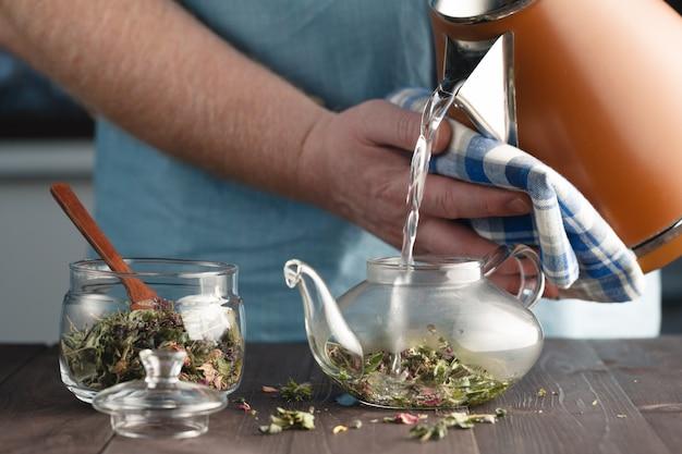 Mężczyzna warzy herbaty ziołowe w czajniku