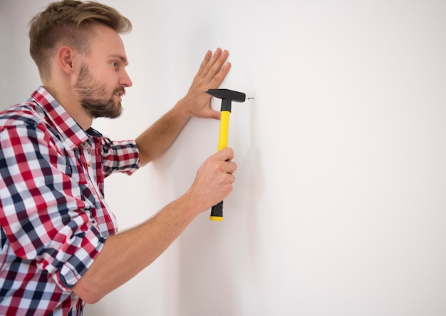 Mężczyzna wbija gwóźdź w ścianę