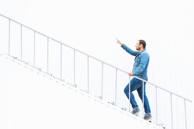 Mężczyzna wchodzi po schodach, pokazując rękę do przodu