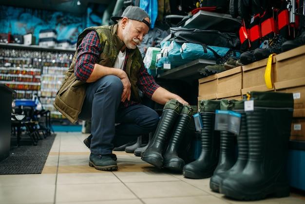 Mężczyzna wędkarz wybiera kalosze w sklepie wędkarskim