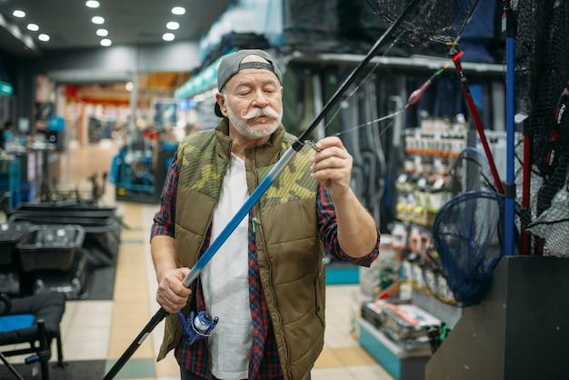 Mężczyzna wędkarz zakłada żyłkę w ucho wędki w sklepie wędkarskim.