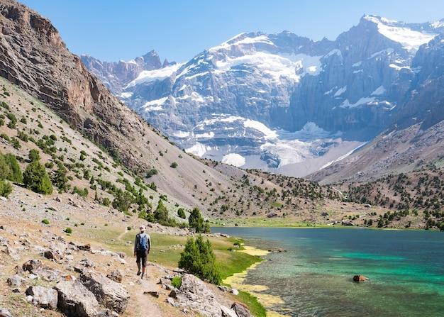 Mężczyzna wędrujący po jeziorach kulikalon w górach fann, tadżykistan