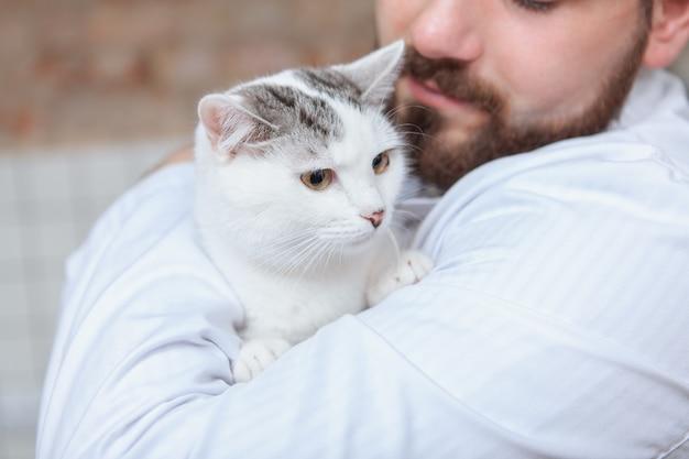 Mężczyzna weterynarz z kotem w swojej klinice