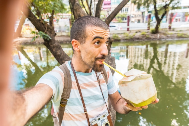 Mężczyzna weź selfie i wypij wodę kokosową w bangkoku