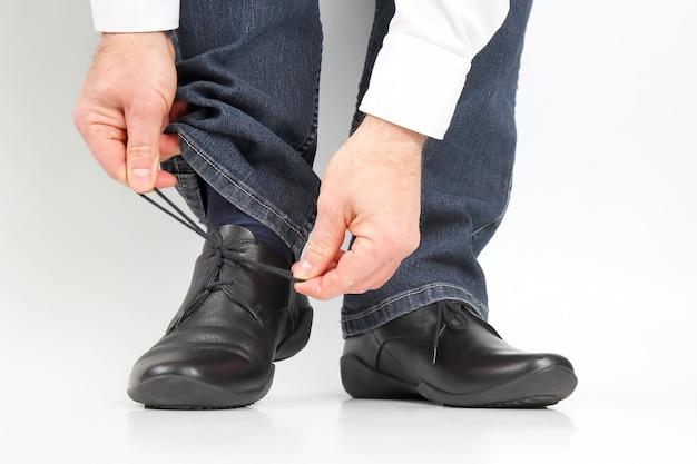 Mężczyzna wiązał sznurówki na klasycznych butach