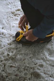 Mężczyzna wiązany sznurowadłami butów trekkingowych