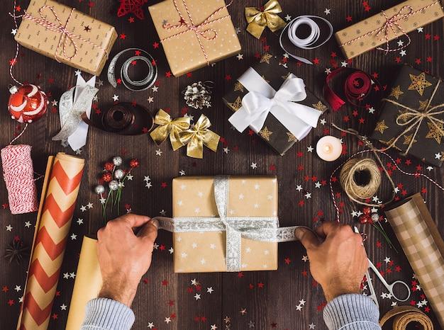 Mężczyzna wiąże łęk na boże narodzenie prezenta pudełka procesie pakunku nowego roku prezenta pudełko
