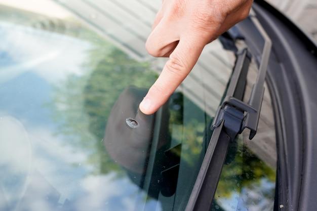 Mężczyzna widzi wypadek samochodowy z powodu uszkodzenia kamienia uszkodzonej szyby podczas jazdy