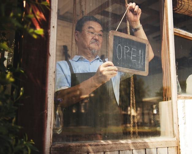 Mężczyzna wiesza otwartego znaka w kwiatu sklepie