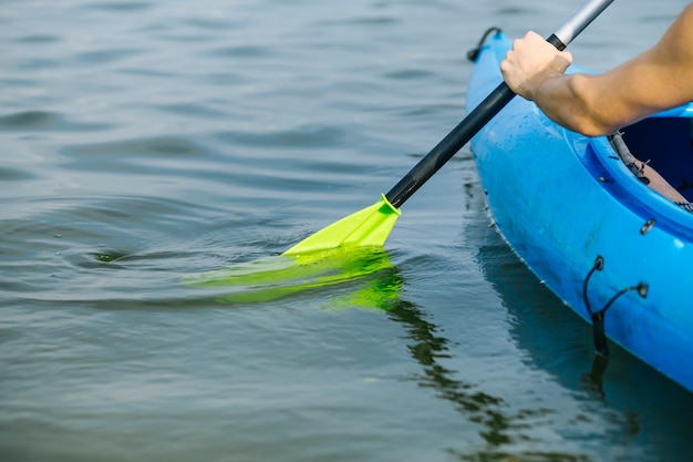 Mężczyzna wiosłowanie kajakiem nad jeziorem