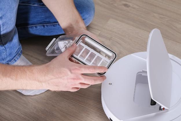 Mężczyzna wkłada filtr i pojemnik, aby zbierać kurz i zanieczyszczenia do robota odkurzającego.
