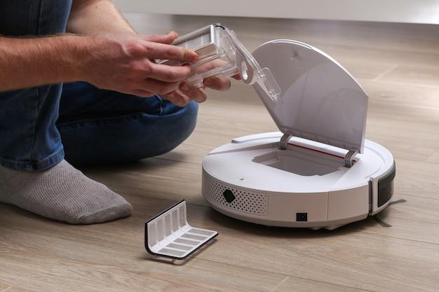 Mężczyzna wkłada filtr i pojemnik, aby zebrać kurz i zanieczyszczenia do robota odkurzającego.