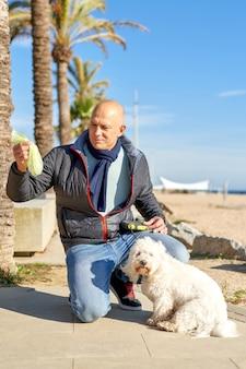 Mężczyzna wkłada kupę do torby dla swojego psa w parku.