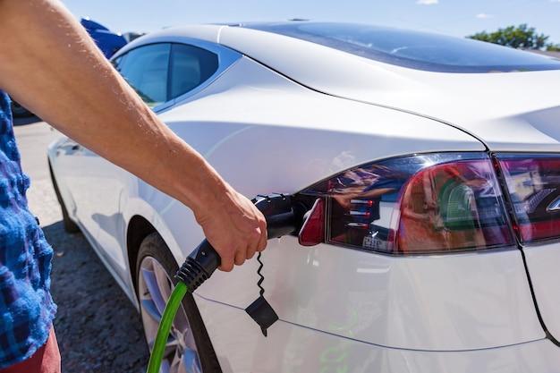 Mężczyzna wkłada ładowarkę do pojazdu elektrycznego. stacja ładowania pojazdów elektrycznych do domu z tłem samochodu ev