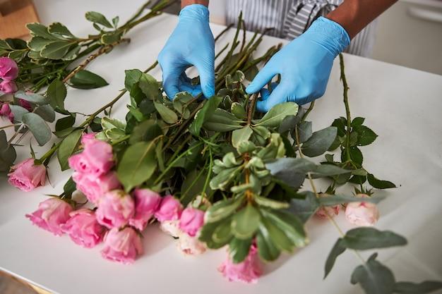 Mężczyzna wkłada lateksowe rękawiczki, gdy tworzy świeże bukiety różowych róż