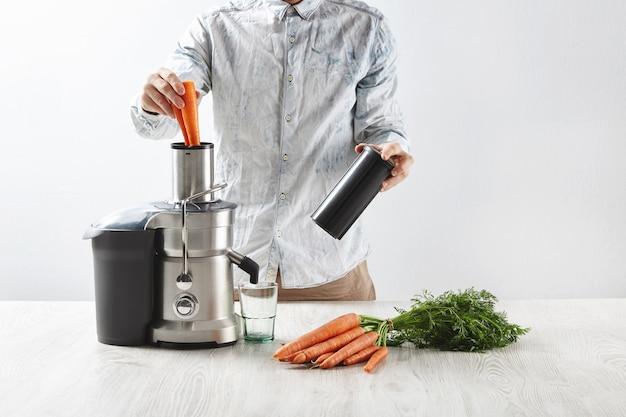 Mężczyzna wkłada marchewki do metalowej wyciskarki z pustą szklanką, aby zrobić smaczny sok na śniadanie