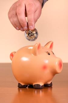 Mężczyzna wkłada marszczyć monetę w piggy bank