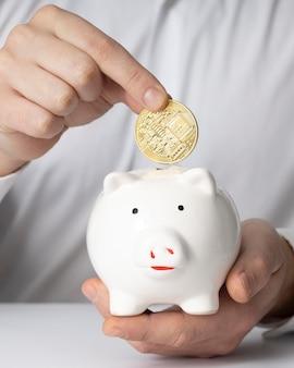 Mężczyzna wkłada monetę do skarbonki