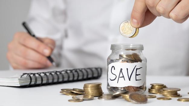 Mężczyzna wkłada monetę do słoika oszczędnościowego