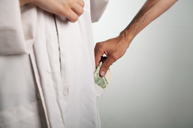 Mężczyzna wkłada pieniądze do kieszeni lekarza