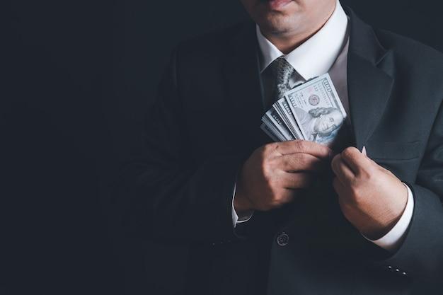 Mężczyzna wkłada pieniądze z łapówki do kieszeni na czarnej ścianie, koncepcja korupcji, zysk finansowy, kaucja i przestępczość