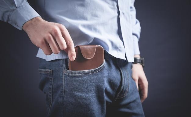 Mężczyzna wkłada portfel do kieszeni.