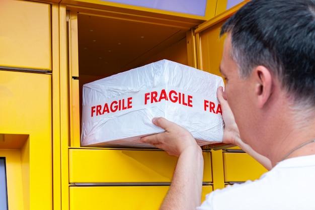 Mężczyzna wkłada pudełko do samoobsługowej skrzynki pocztowej