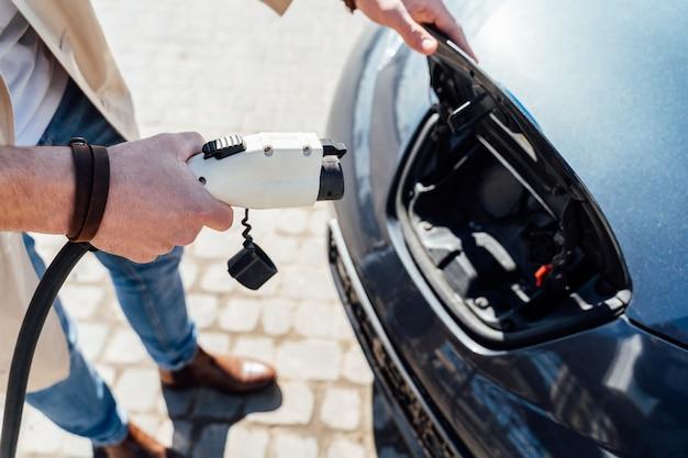 Mężczyzna wkłada wtyczkę do samochodu elektrycznego